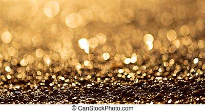 Sparkling light boke blur. Golden glitter particles background.