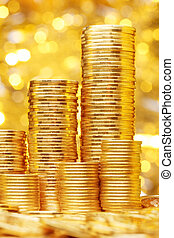 Sparkling new golden coins stacks on bright light glowing...