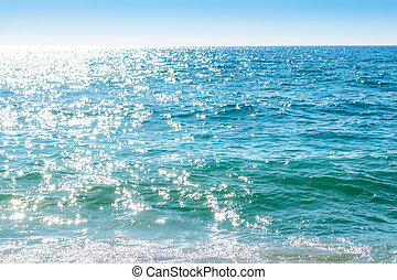 Sparkling rippled water surface in bright blue colors