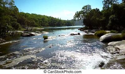 sparkling river rapids run under sun rays against landscape
