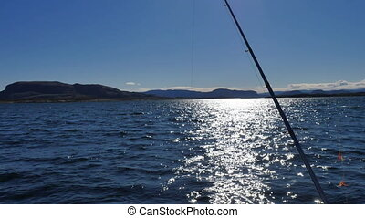 Sparkling water surface and moving  fishing rod