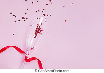 Sparkling wine glass with snal red star shaped confetti on pink background,