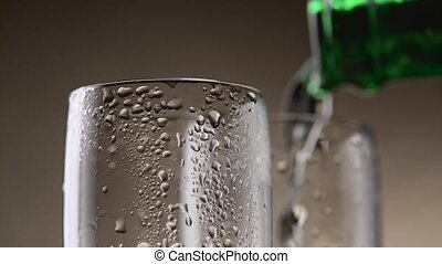 Sparkling wine pours from a green bottle in two steamy...