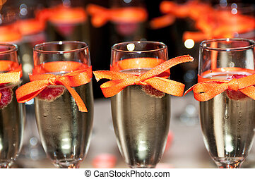 Sparkling wine with raspberry, ribbon decorated champagne...