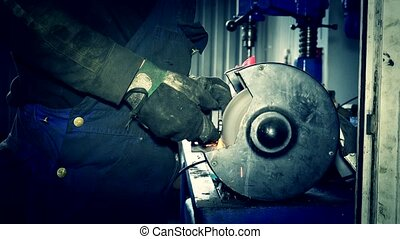 Sparks come out from grinding wheel. Mechanic polish brake pads.