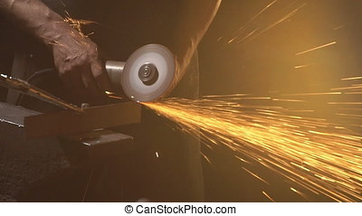 Sparks from grinder cutting metal. Slow motion