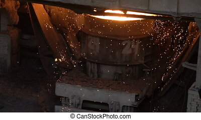 Sparks from hot metal flying out of the vat