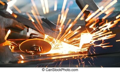 Sparks from welding car parts in a car repair shop. Detail...