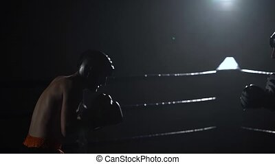 Sparring in the ring between two guys in a dark ring, they...