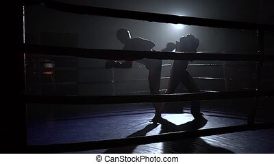 Sparring in the ring between two guys in a dark space, they...