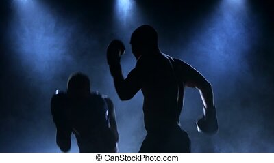 Sparring of two boxers in the studio. Silhouette, smoke
