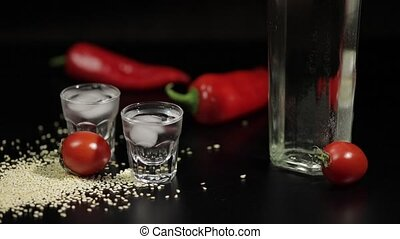 Sparse sesame seeds to two cups of vodka near bottel with...