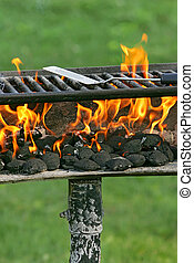 Spatula on Flaming Barbecue Grill - Cropped image of an old...
