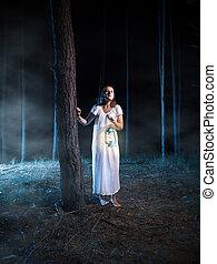 spaventato, donna camminando, in, nebbioso, notte, foresta, con, lanterna