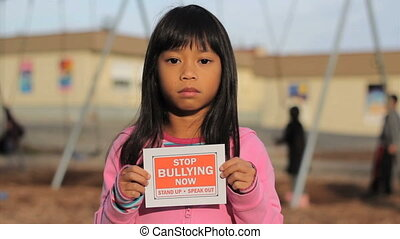 Speak Out Against Bullying - A sad little girl holds up a...