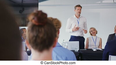 Speaker addressing the audience at a business conference - ...