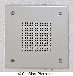 Speaker grille mounted on stippled ceiling