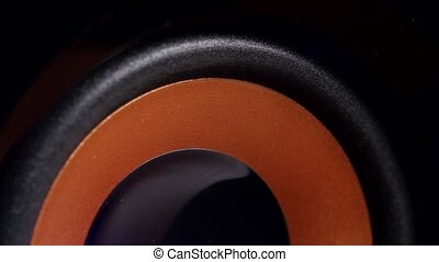 Speaker membrane movement, speaker playing loud music with bass, speaker cone vibrating, closeup
