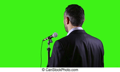 Leader in front of mic gives speech, dealing with the fear of public speaking with green screen