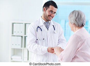 Speaking with patient - Confident doctor looking at his...