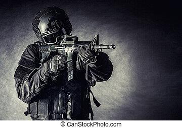 Spec ops police officer SWAT in black uniform and face mask