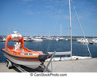 Special boat on the background of yachts in marina facilities