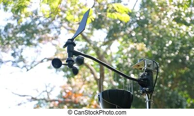 professional meteorological instrument with cap anemometer measures wind strength and direction against green trees on sunny day close view