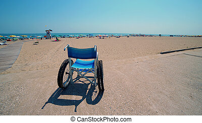 Special cast wheelchair on the sandy beach of the tourist resort