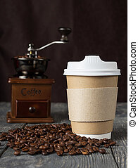 Special container for take-away coffee, beans of coffee and hand mill on table