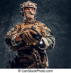 Special forces soldier in camouflage uniform holding a gun with a flashlight and looking sideways. Studio photo against a dark textured wall