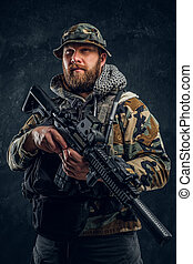 Special forces soldier in the military camouflaged uniform holding an assault rifle. Studio photo against a dark textured wall