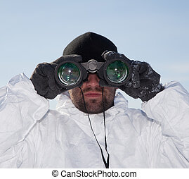 Special Forces soldier in white camouflage looking through binoculars against blue sky