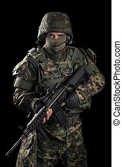 Special forces soldier with gun on dark background