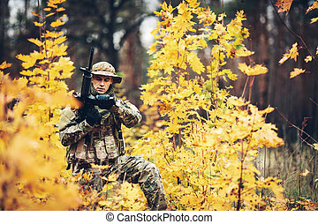 soldier with rifle in the forest