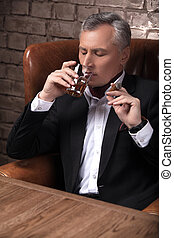 Special moments. Confident mature businessman drinking whiskey and smoking a cigar