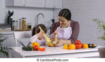 Happy little daughter with down syndrome stirring fresh salad while preparing healthy food together with cheerful mother in the kitchen. Caring mother teaching her special needs child cooking.