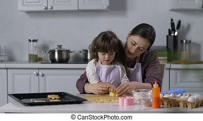 Special needs child with mother cutting out cookies