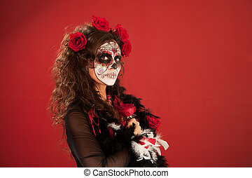 Woman in makeup for Dia De Los Muertos holds a rose close to herself