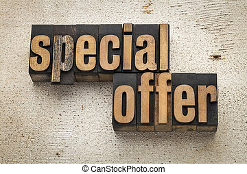 special offer sign in vintage letterpress wood type on a grunge painted barn wood background