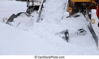 Tractor with snowplow equipment removing snow from streets in snow blizzard.