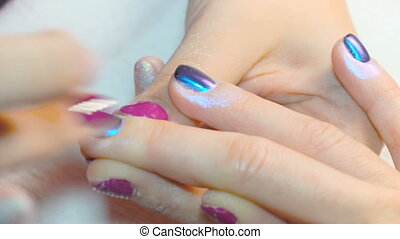specialist beauty makes a woman a manicure. rubbing shining...