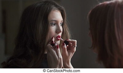 Lip gloss application. Backstage of fashion industry.