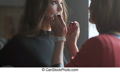 Specialist doing makeup for model. Lip gloss application.