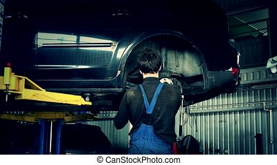 Specialist guy working under lifted car in garage. Color...