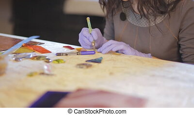 specialist in working with glass and small stones work  at his desk, she creates jewelry, brooches, pendants, bracelets stained-glass windows stained glass
