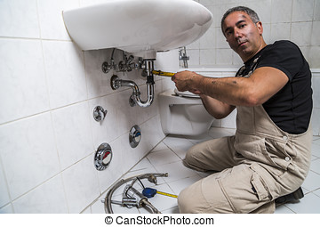 specialist male plumber repairs faucet in bathroom