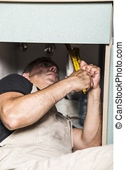 specialist male plumber repairs faucet in kitchen