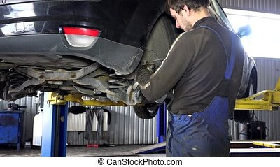 specialist mechanic repairing customer car brake system.