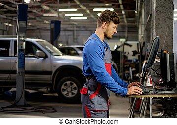 Specialist near car diagnostic pc in a workshop