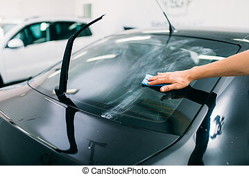 Specialist prepairs the window, car tinting film - Male...